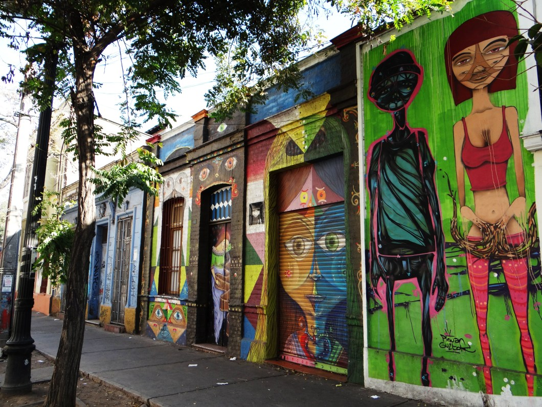The buildings are covered in brightly coloured graffiti