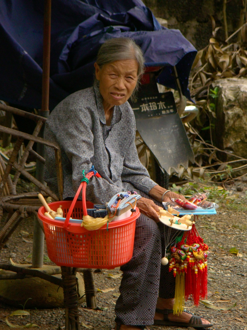 Lady sitting outside the house selling some souveniers.